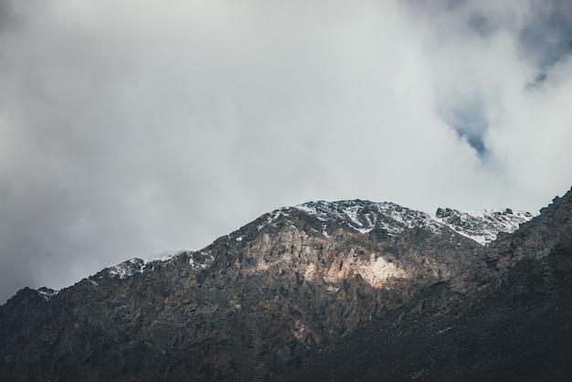 日光の下で雪と低い雲が上にある岩のある山の風景。日差しの中で鋭い岩のある素晴らしい岩壁。雲の中に高い岩山の頂点がある大気の山の風景。