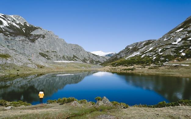 눈 덮인 산과 호수와 산 풍경입니다. 호수를보고 노란색 코트를 가진 여자입니다. 레온, 이소 바 호수. 스페인.
