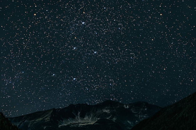 Mountain. night sky with stars and moon and clouds.
