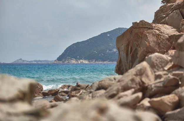 Гора на берегу моря на юге сардинии, летом фильтруется скалами с морскими волнами.
