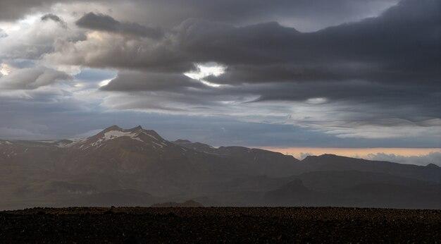 Пик горы со снегом и облаками во время драматического и красочного заката на пешеходной тропе лейгавегур недалеко от торсморка.