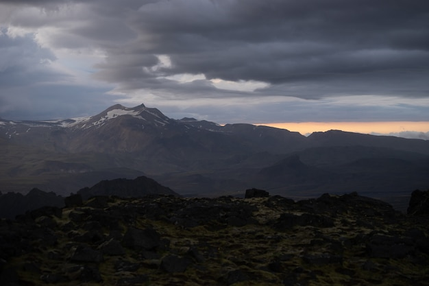 Пик горы со снегом и облаками во время драматического и красочного заката.