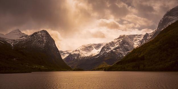 Горные вершины в снегу. живописный пейзаж. фьорд в норвегии. натуральные обои. горный скандинавский пейзаж