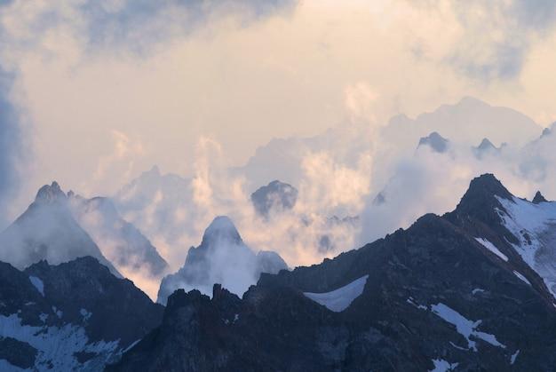 Горные вершины на кавказе ранним утром над облаками