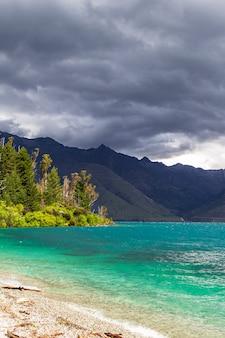 Горные вершины над бирюзовой водой дождливый день на озере вакатипу, новая зеландия