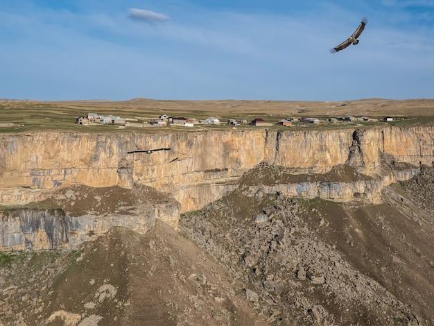 崖の上の村のある山の高原。ワシは山の峡谷の上を飛ぶ。フンザフ。ダゲスタン。