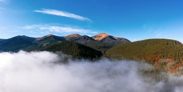 푸른 하늘에 대 한 산맥입니다. 공중보기에서 산 봉우리, 숲과 낮은 구름의 자연 풍경.