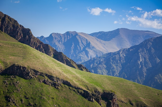山脈と青い空を背景に緑の丘