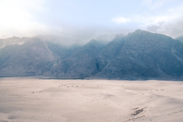 Mountain range in the fog. katpana cold desert at sarfaranga, skardu. gilgit baltistan, pakistan.