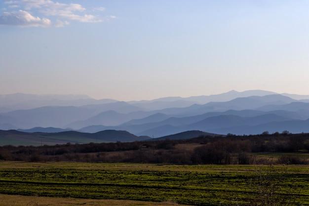 日没時の山脈の風景、山と丘のラインのビュー