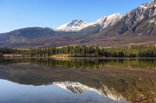 Горный хребет с отражением соснового леса на озере пирамид в национальном парке джаспер, канада