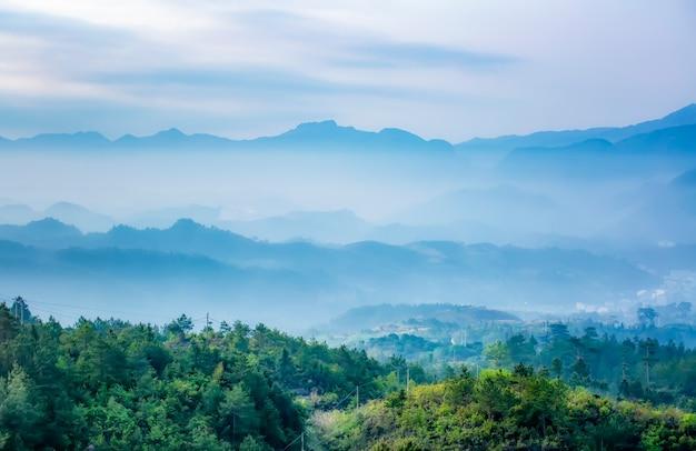 朝の色鮮やかな霧の中からシルエットが見える山脈。