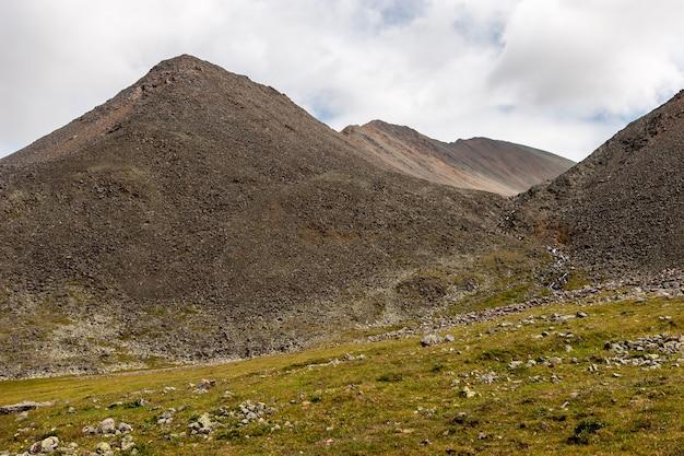 Горные хребты из камней на фоне облаков. зеленый склон с травой и камнями. по горизонтали.