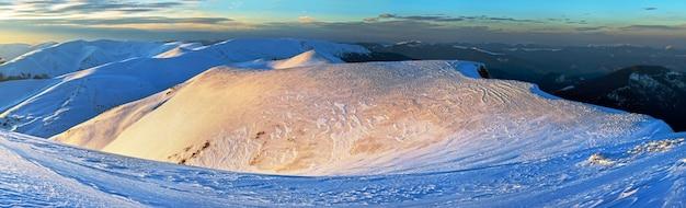 Mountain ridge sunset panorama view in golden-pastel tones from last evening sunrays (ukraine, carpathian mt's, drahobrat ski resort). ten shots stitch image.
