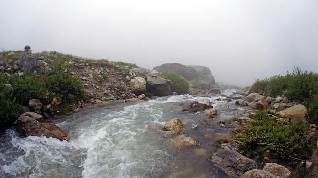 霧の中の山の川。コーカサス