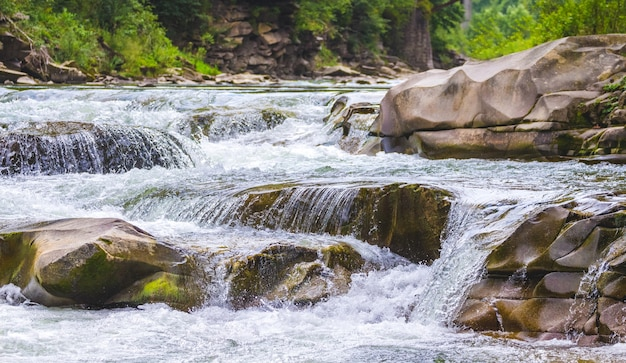 Mountain river with a small waterfall in summer