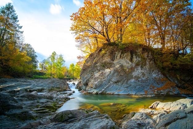 Горная река с небольшим водопадом с прозрачной бирюзовой водой, падающей между мокрыми валунами с густой белой пеной в осенний яркий день.