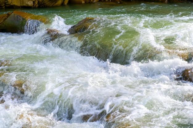 Горная река с небольшим водопадом с прозрачной бирюзовой водой, падающей между мокрыми валунами с густой белой пеной.