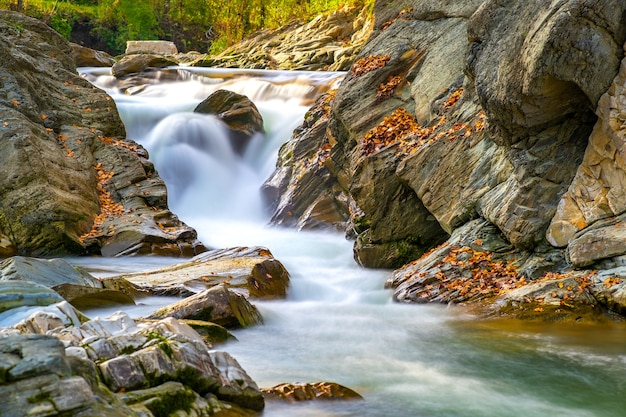 Mountain river with small waterfall with clear turquoise water falling down between wet boulders with thick white foam on autumn bright day.