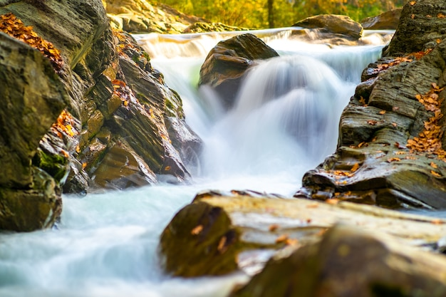 Mountain river with small waterfall with clear turquoise water falling down
