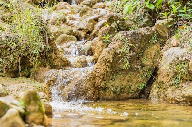 Горная река с каменными каскадными водопадами. естественный фон в солнечный день. эталонное изображение для цифровой живописи.