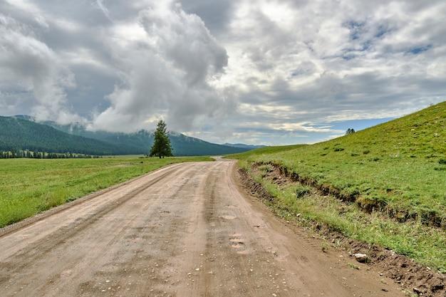 Горная дорога размыта дождями. бездорожье в горах. мрачное облачное небо и дождь в горах. алтай