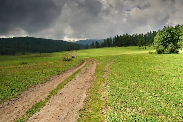 雨でぼやけている山道。山のオフロード。暗い曇り空と山の雨。アルタイ