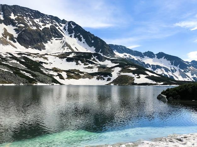Paesaggio di montagna che si riflette nell'acqua, pittoresca natura invernale del parco nazionale dei tatra