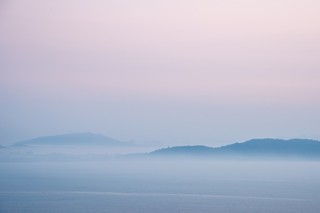 Mountain and sea covered with morning mist before sunrise.