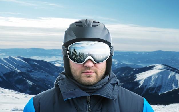 ゴーグルに反射する山に対するマウンテンスキーヤー