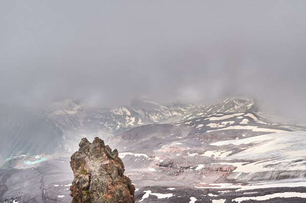 Mountain slopes and black volcanic rock covered with snow. low clouds over the rutted peaks. elbrus