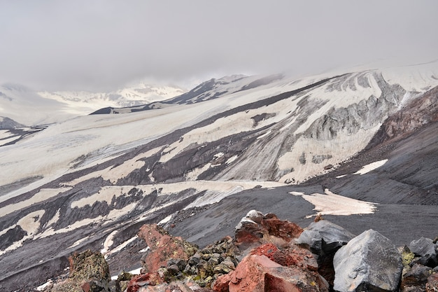 Mountain slopes and black volcanic rock covered with snow.