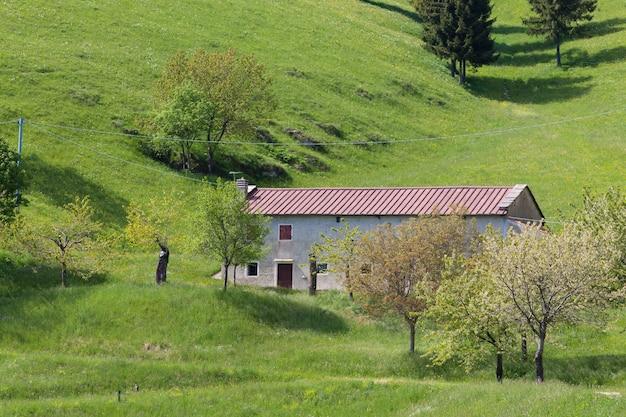 Панорама горного источника, зеленые холмы и сельское здание