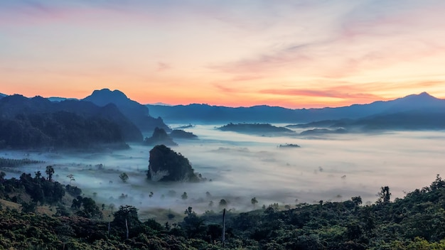 Восход горы с красивым драматическим небом. утренний туман в горной долине перед восходом солнца в зимний сезон. горный пейзаж фу лангка с утренним морем тумана на заднем плане
