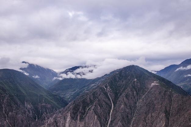 Гора в окружении облаков на рассвете в шангри ла, провинция юньнань, китай