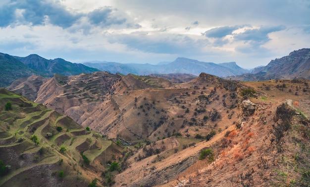 マウンテンテラス。まばらな植生に覆われた赤い織り目加工の山々を背景に、遠くまで伸びる岩だらけの棚。全景。ダゲスタン。