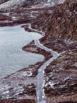 マウンテントレイル。航空写真。雪に覆われた北極の丘の間の曲がりくねった山道。