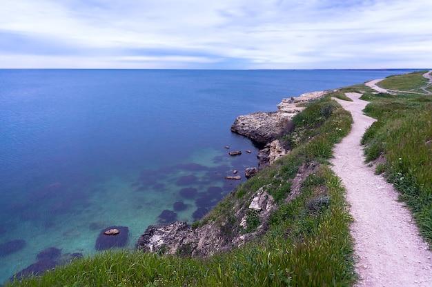 海を背景にした丘の中腹の登山道