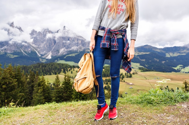 Mountain trip fashion details, blonde woman posing near alp mountains.