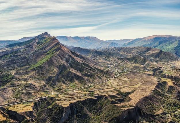 山の谷。まばらな植生に覆われた山々を背景に、遠くまで伸びる岩だらけの棚。谷を渡る道。航空写真。