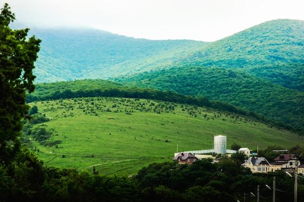 丘の上に緑の野原がある春の山の谷。丘のふもとにあるエレベーターと家。