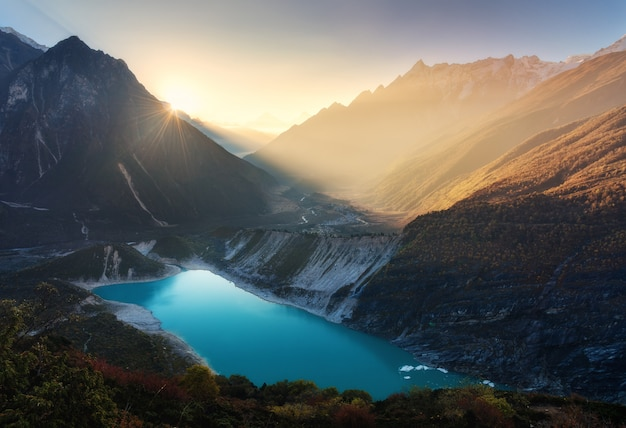 Mountain valley and lake with turquoise water at sunrise in nepal