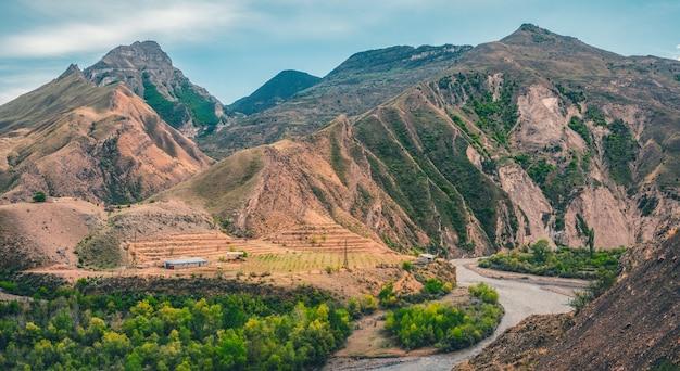 川のある山の谷。高山、複雑な山の風景、緑豊かな植生に覆われた斜面。全景。