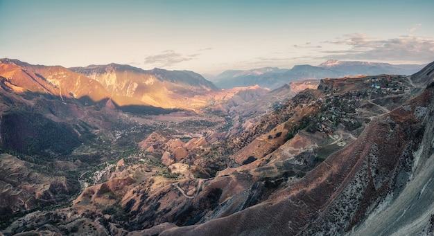 赤い山と山の谷。曲がりくねった道のある山の谷の朝のパノラマビュー。マトラス渓谷。ダゲスタン。