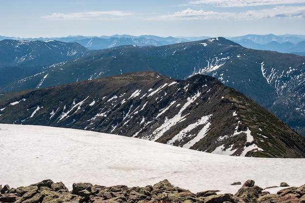 雪の帯からの山の景色、山の斜面に雪があります