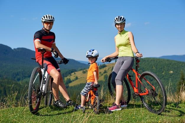 Молодые современные велосипедисты, мама, папа и ребенок туристов семьи отдыхая на велосипедах смотря в камере на травянистом холме на далекой предпосылке mountain view. активный образ жизни, путешествия и концепция счастливых отношений.