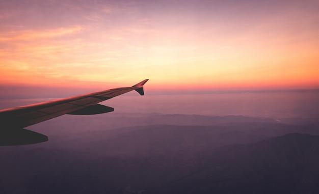 Крыла самолета в небе и сцена mountain view в восходе солнца.