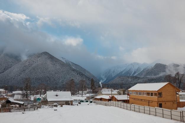 Горные деревенские дома в снежном зимнем лесу в горах в снежном утреннем тумане
