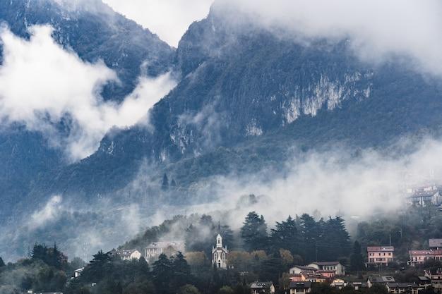 霧の日の山の村、ロンバルディアの北にあるイタリアアルプス。ヨーロッパの村の町