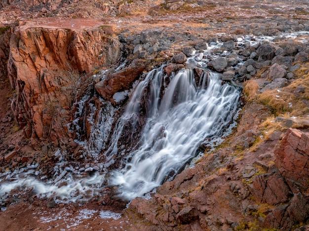 山の滝の川の小川の眺め。凍った山の滝